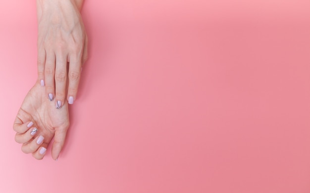 Schöne, sanfte weibliche hände auf rosa