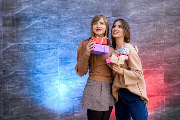 Schöne sankt-mädchen mit geschenkboxen und funkelnder girlande, die das neue jahr feiert
