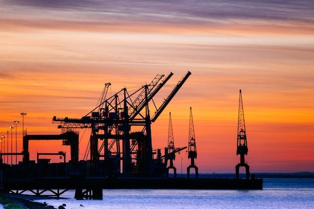 Schöne schattenbild der hafenmaschinerie während des sonnenuntergangs