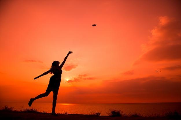 Schöne schattenbild der jungen frau, die papierflugzeug wirft.