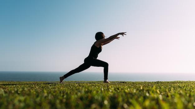 Schöne schattenbild einer frau auf dem hintergrundhimmel, der yoga praktiziert. speicherplatz kopieren