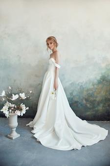 Schöne schlanke blondine in der abendsonne in einem langen weißen kleid.