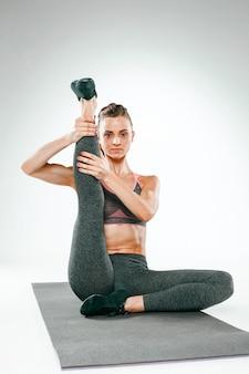 Schöne schlanke brünette, die einige dehnübungen in einem fitnessstudio macht