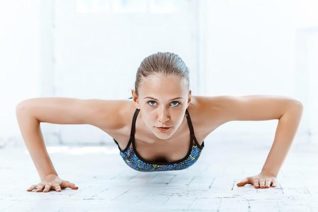 Schöne schlanke brünette, die einige liegestütze im fitnessstudio macht