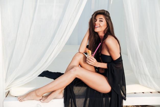 Schöne schlanke brünette frau, die im badeanzug mit langen haaren auf strandbett an der küste und trinkcocktail aufwirft