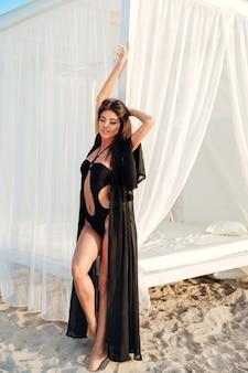 Schöne schlanke brünette frau, die im badeanzug mit langen haaren nahe strandbett an der küste aufwirft