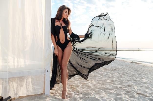Schöne schlanke brünette frau, die im badeanzug und im schwarzen schal nahe strandbett an der küste aufwirft