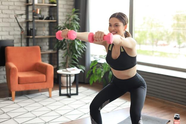 Schöne schlanke fitnessfrau hockt mit hanteln. sport, gesunder lebensstil. mädchen macht zu hause sport.