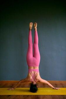 Schöne schlanke form, die kopfstand-yoga-pose tut