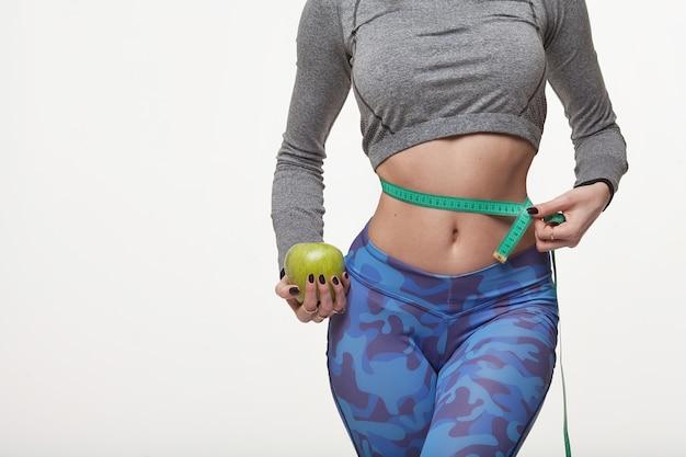 Schöne schlanke frau, die grünen apfel und mit mehreren farbmessbändern auf ihrer taille hält