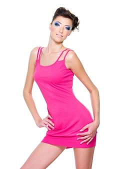 Schöne schlanke frau, die im rosa kleid lokalisiert auf weiß aufwirft