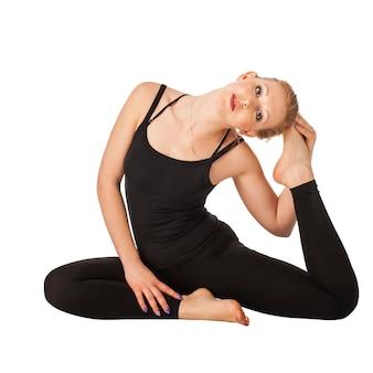 Schöne schlanke frau, die yoga lokalisiert lokalisiert auf weiß tut