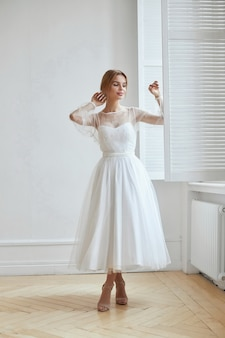 Schöne schlanke frau im weißen hochzeitskleid, neue sammlung von kleidern für die braut. lärm, unscharf