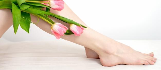 Schöne schlanke glatte frauenbeine mit tulpenblumen auf weißem hintergrund