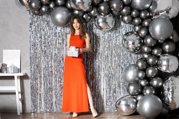 Schöne schlanke junge brünette frau im roten kleid hält geschenkbox in händen auf einem silbernen glänzenden hintergrund mit runden luftballons.