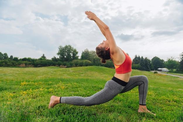 Schöne schlanke und gesunde yoga-frau, die sonnengruß am warmen sommermorgen durchführt