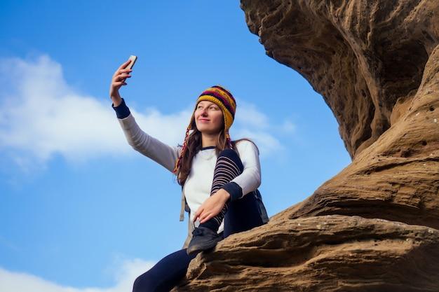 Schöne schlanke und sportliche junge touristenfrau in einem lustigen hut aus nepalesischem wollyak sitzt und ruht sich aus und macht selfie-telefon, das große klettersteige auf felsbrocken-canyon-steinen himmelshintergrund klettert