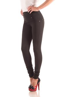 Schöne schlanke weibliche beine in beigen leggings mit hohen absätzen auf weiß