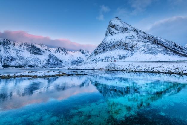 Schöne schneebedeckte berge und blauer himmel mit wolken, die in der dämmerung im wasser reflektiert werden.