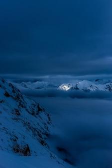 Schöne schneebedeckte hügel und berge bei nacht mit atemberaubendem bewölktem himmel