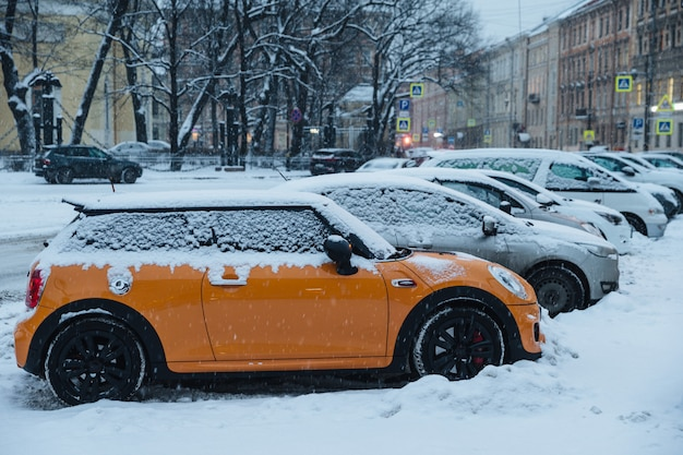 Schöne schneebedeckte stadt bei winterwetter. autos auf dem parkplatz mit dichtem schnee bedeckt