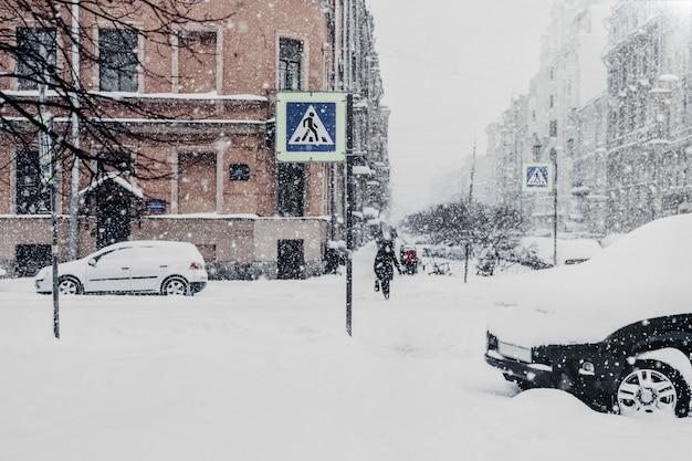 Schöne schneebedeckte stadt mit dem transport und leuten, bedeckt mit starkem weißem schnee während des blizzards