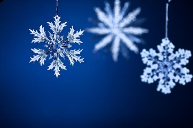 Schöne schneeflocken auf blauem hintergrund mit farbverlauf. weihnachtskonzept