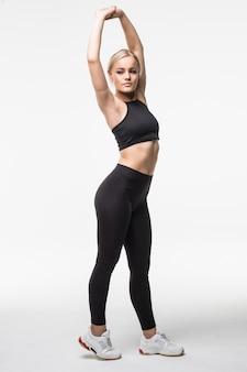 Schöne schöne junge blondine macht verschiedene aktobatische übungen, die sich auf armen und beinen auf weiß strecken