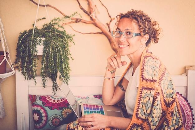 Schöne schöne kaukasierin mittleren alters setzt sich mit einer abdeckung auf der schulter für die frühlingskälte hin und arbeitet mit einem farbigen laptop auf der terrasse. lächeln und glücklich, auf alternative weise zu hause zu arbeiten