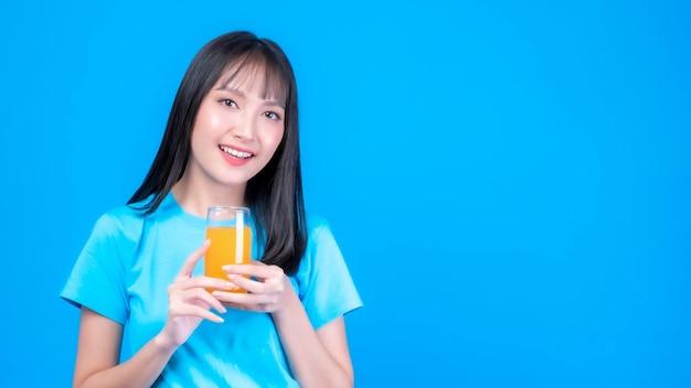 Schöne schönheit asiatische frau süßes mädchen mit ponyfrisur in blauem hemd fühlen sich glücklich, orangensaft für eine gute gesundheit zu trinken, auf blauem hintergrund mit kopienraum - lifestyle-schönheitsfrau-gesundheitskonzept