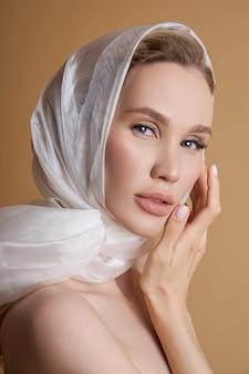 Schöne schönheit blonde frau mit einem großen weißen kopftuch, weißes tuch