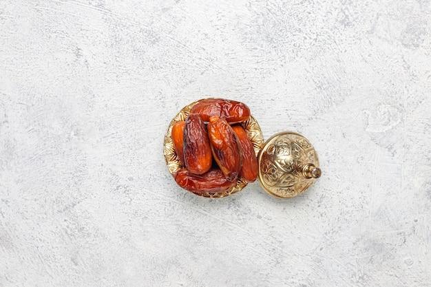 Schöne schüssel voll von dattelfrüchten, die ramadan symbolisieren, draufsicht