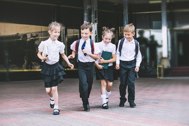 Schöne schulkinder aktiv und glücklich auf dem hintergrund der schule in der uniform