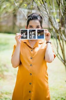 Schöne schwangere asiatische frau, die ultraschallscanbilder hält