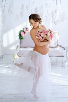Schöne schwangere frau am zarten innenraum