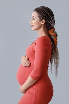 Schöne schwangere frau auf grauem hintergrund