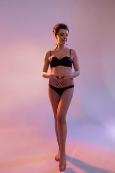 Schöne schwangere frau berührt ihren bauch und schaut im studio mit kollourösem licht zur seite