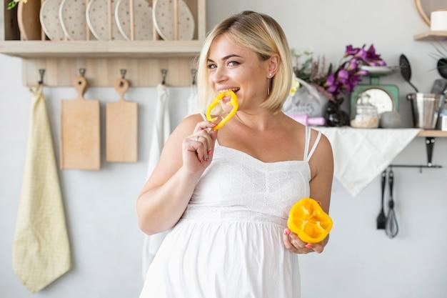 Schöne schwangere frau, die gelben pfeffer isst