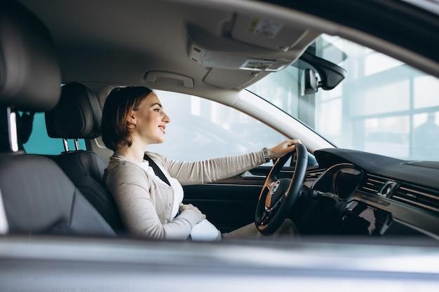 Schöne schwangere frau, die im auto fährt