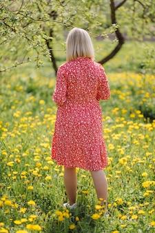 Schöne schwangere frau, die im park das rote kleid trägt Premium Fotos