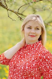 Schöne schwangere frau, die im park das rote kleid trägt