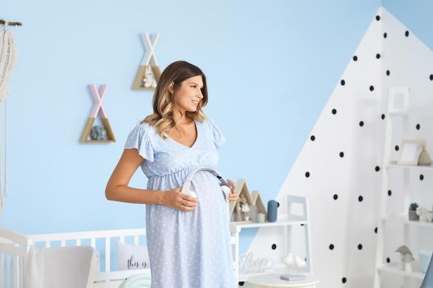 Schöne schwangere frau, die kopfhörer auf ihren bauch zu hause setzt