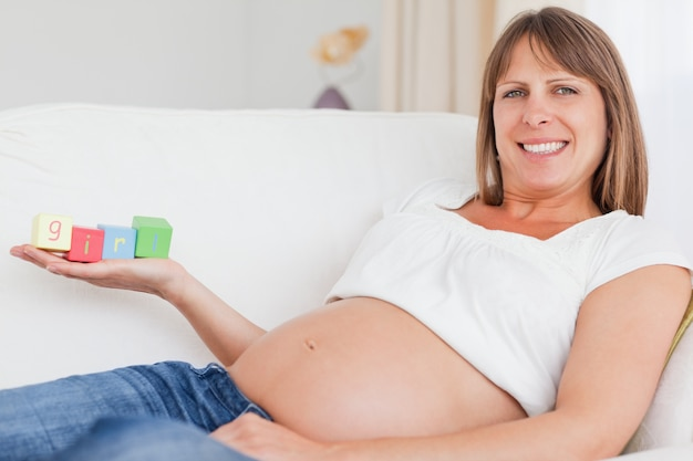 Schöne schwangere frau, die mit hölzernen blöcken spielt und das wort