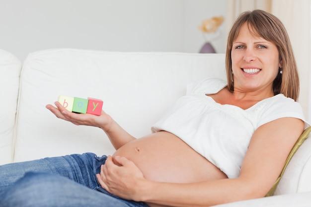 Schöne schwangere frau, die mit holzklötzen spielt und das wort