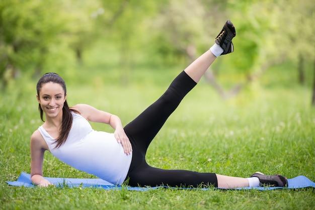 Schöne schwangere frau, die sport im sommerpark tut.