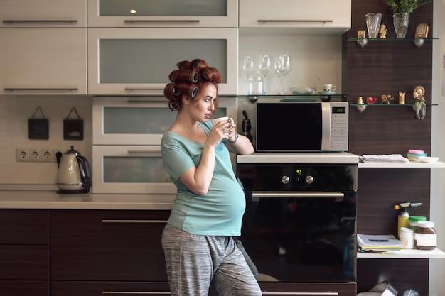 Schöne schwangere frau, die zu hause mit einer tasse tee entspannt