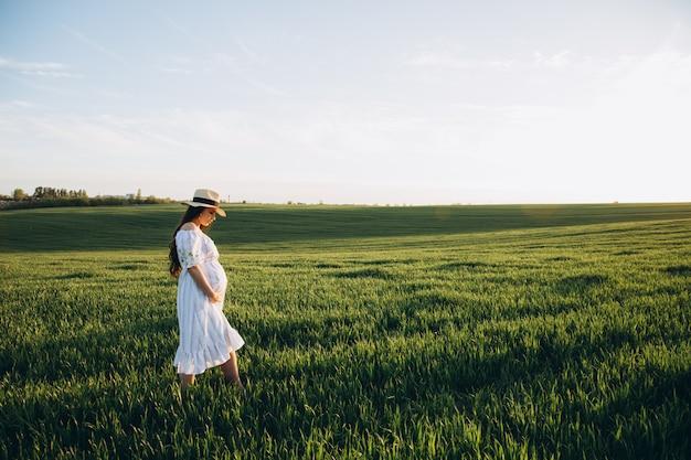 Schöne schwangere frau im frühlingsnaturfeld auf sonnenuntergang