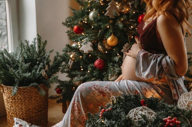 Schöne schwangere frau in der bequemen kleidung, die auf einer tabelle nahe dem weihnachtsbaum sitzt.