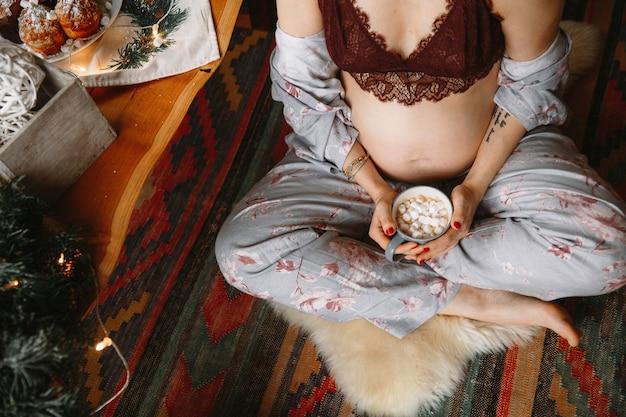 Schöne schwangere frau in der bequemen kleidung, die nahe der tabelle ander der weihnachtsbaum sitzt.