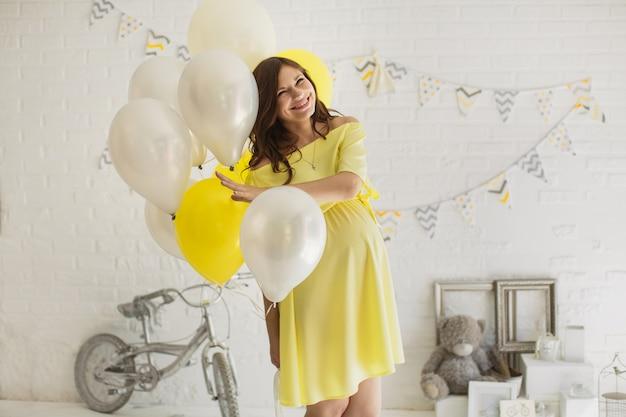 Schöne schwangere frau in einem gelben kleid im studio